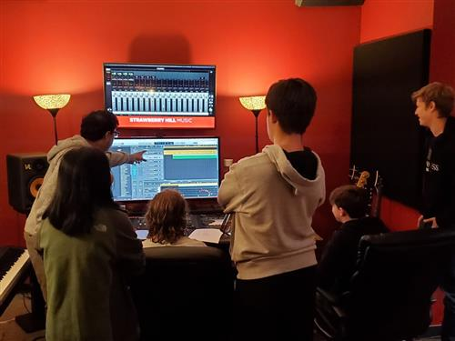 Students watching screen in audio production studio